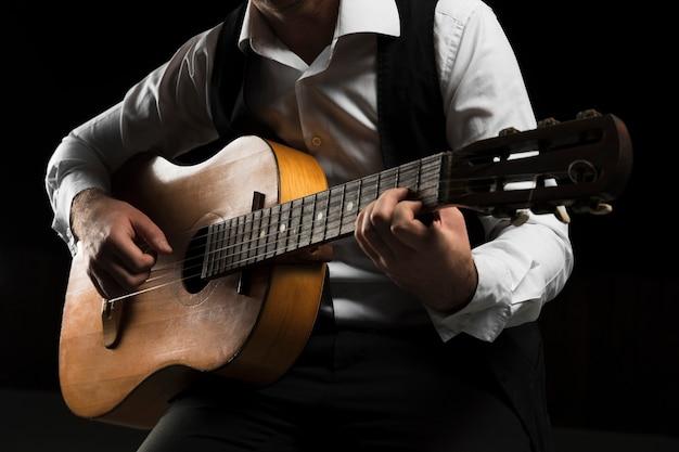 Homem vestindo roupas de palco tocando guitarra Foto Premium