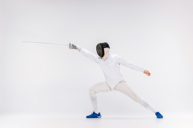 Homem vestindo terno de esgrima a praticar com espada contra cinza Foto gratuita