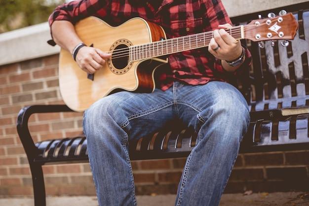 Homem vestindo uma flanela vermelha e preta sentado em um banco tocando violão Foto gratuita