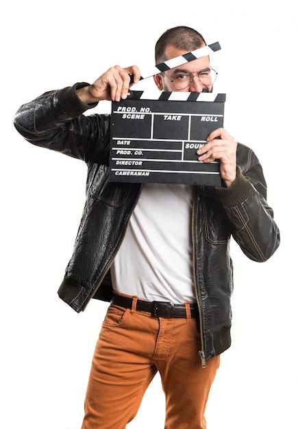 Homem vestindo uma jaqueta de couro segurando um clapperboard Foto gratuita