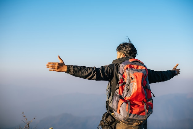 Homem viajando com mochila caminhadas nas montanhas Foto gratuita