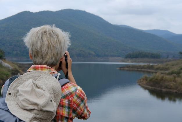 Homem viajante com mochila viagem no lago. mochileiro de turista usar câmera para tirar foto. Foto Premium