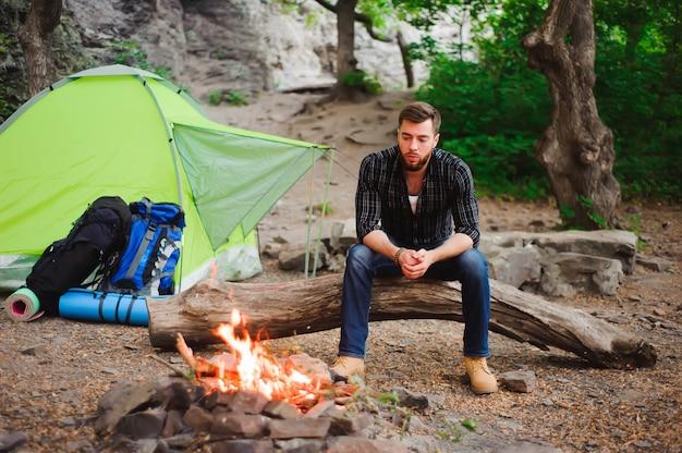 Homem viajante relaxante, olhando para o fogo e sonhando na barraca de acampamento ao ar livre na natureza Foto Premium