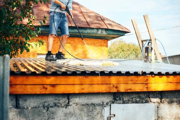 Homem wach tapete limpo ao ar livre no telhado com água Foto Premium