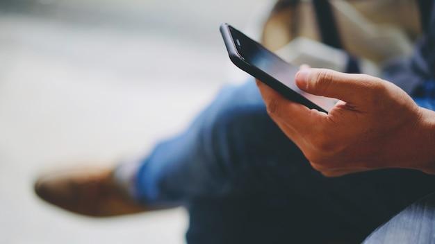 Homem, waring, calças brim, usando, smartphone, com, mão esquerda, espaço cópia, ligado, esquerda Foto Premium