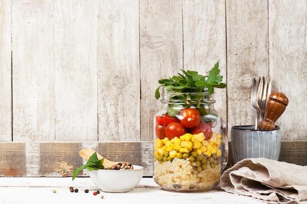 Homemade salada saudável camada em frasco de pedreiro em um fundo de madeira Foto gratuita
