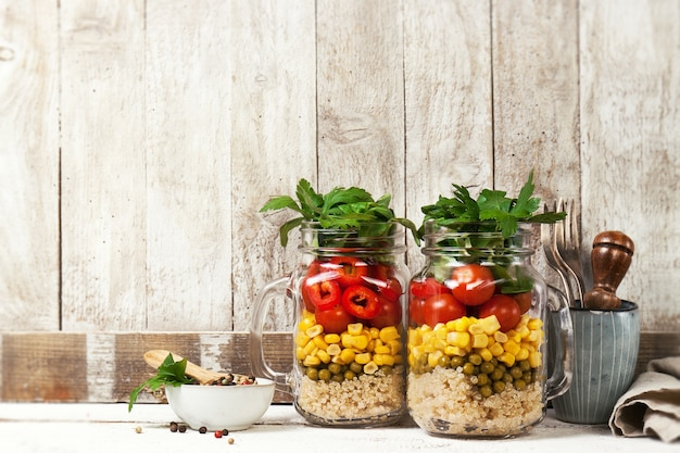 Homemade salada saudável camada em frascos em um backgroun de madeira Foto gratuita