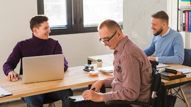 Homens adultos positivos trabalhando juntos no escritório Foto gratuita