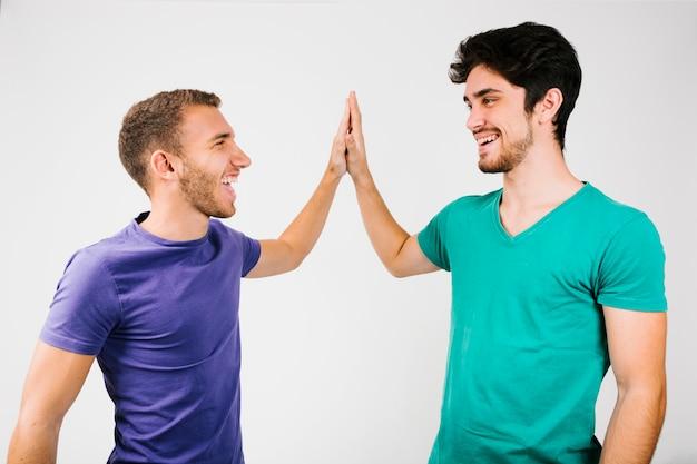 Homens alegres em t-shirts brilhantes dando cinco Foto gratuita