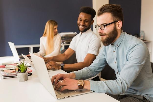 Homens alegres usando laptops Foto gratuita