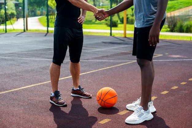 Homens, apertando as mãos na quadra de basquete Foto gratuita