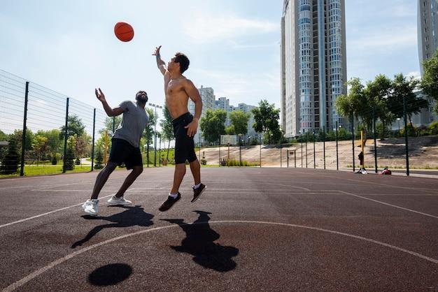 Homens bonitos, jogando bola de basquete Foto gratuita