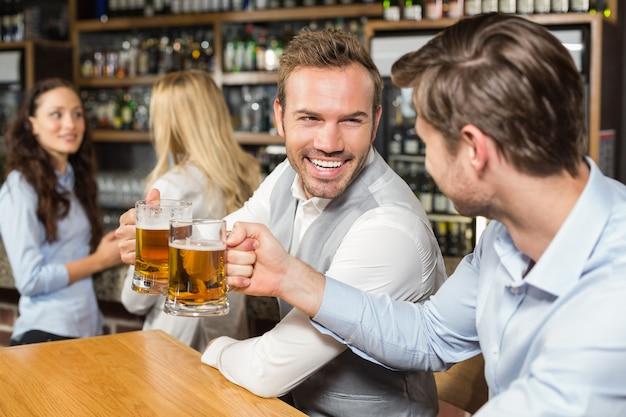 Homens brindando na frente, enquanto as mulheres falam por trás Foto Premium