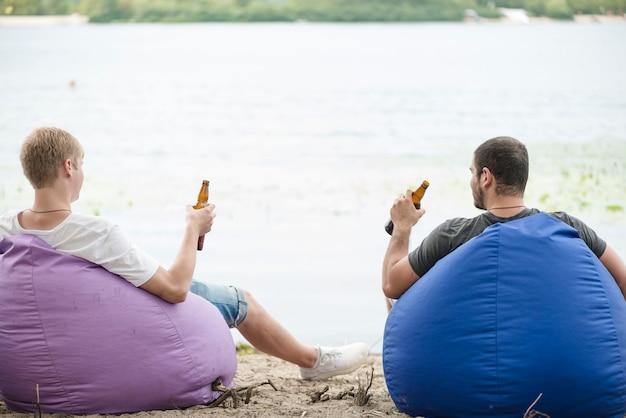Homens com cerveja relaxante em sacos de feijão Foto gratuita