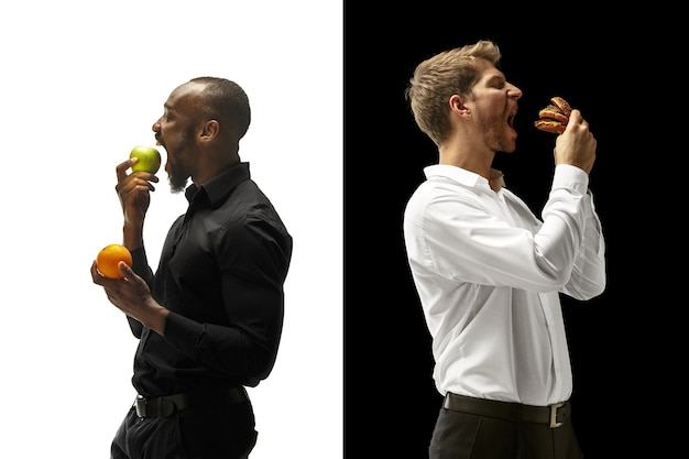 Homens comendo hambúrguer e frutas frescas em um espaço em preto e branco Foto gratuita