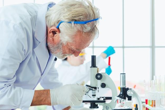 Homens de ciência trabalhando com produtos químicos de microscópios no laboratório Foto Premium
