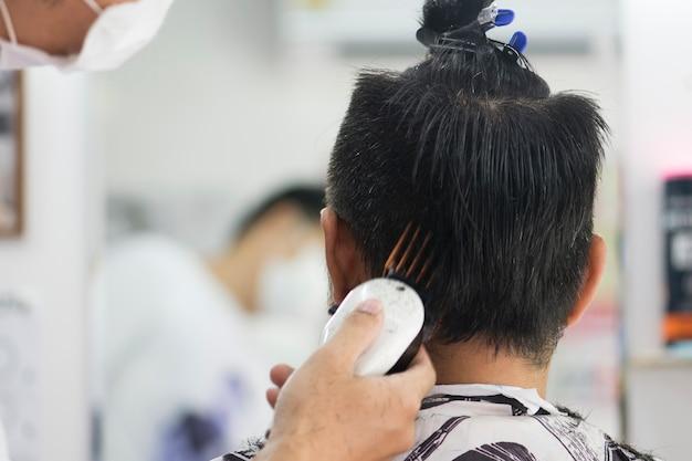 Homens de corte de cabelo barbearia. cabeleireiro masculino; barbeiros. barber corta a máquina do cliente para cortes de cabelo. Foto Premium