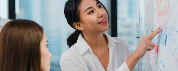 Homens de negócios e mulheres de negócios da ásia que encontram idéias de brainstorming, conduzindo colegas do projeto de apresentação de negócios, trabalhando juntos, planejam a estratégia de sucesso, desfrutam do trabalho em equipe no pequeno escritório moderno. Foto gratuita
