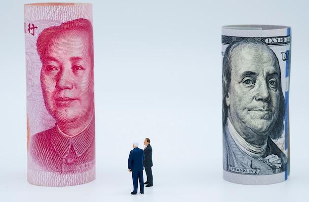 Homens de negócios em miniatura com notas de dólar e china yuan Foto Premium