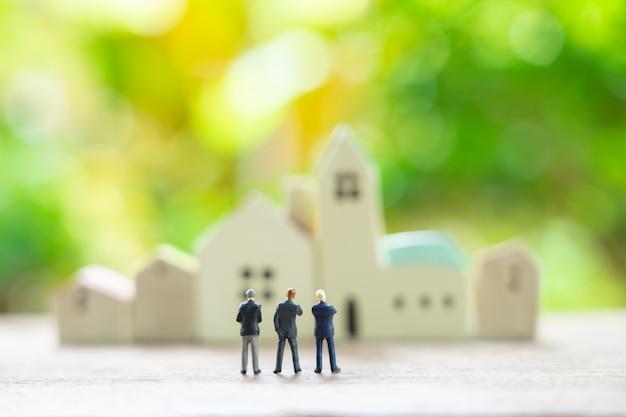 Homens de negócios em miniatura de 3 pessoas em pé com as costas negociando nos negócios. Foto Premium