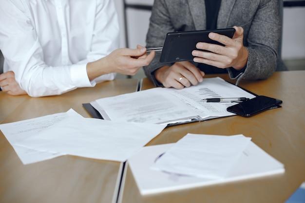 Homens de negócios sentados à mesa dos advogados. pessoas assinando documentos importantes. Foto gratuita