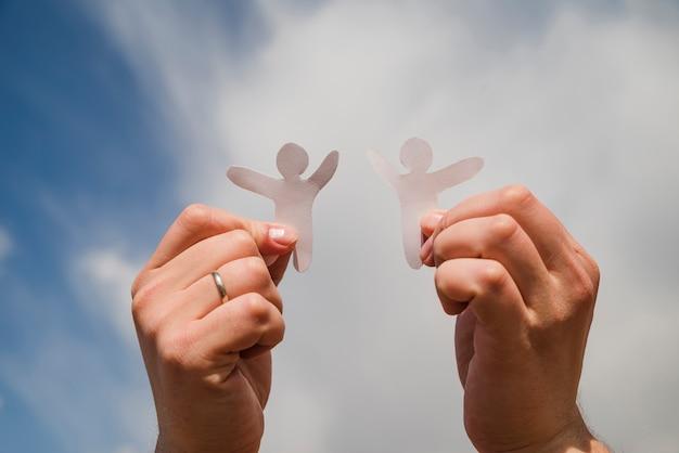 Homens de papel contra o céu Foto gratuita