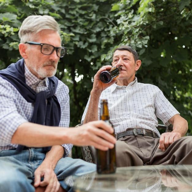 Homens de tiro médio bebendo cerveja Foto Premium