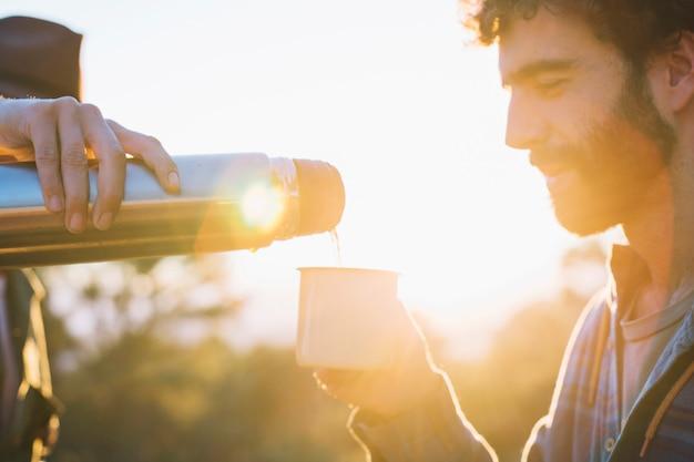 Homens derramando bebida na natureza Foto gratuita