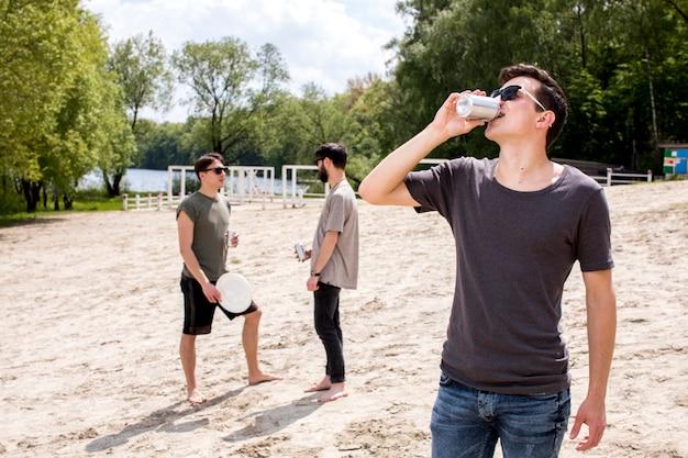 Homens, desfrutando, bebidas, e, segurando, frisbee Foto gratuita