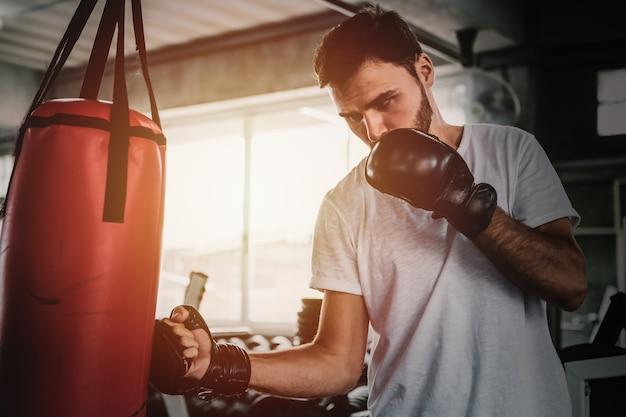 Homens desportivos de retrato com as luvas de boxe de volta a treinar no ginásio Foto Premium