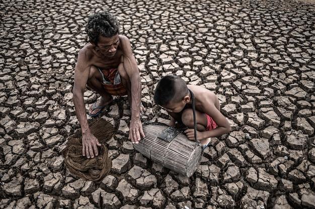 Homens e menino idosos encontram peixes em solo seco, aquecimento global Foto gratuita