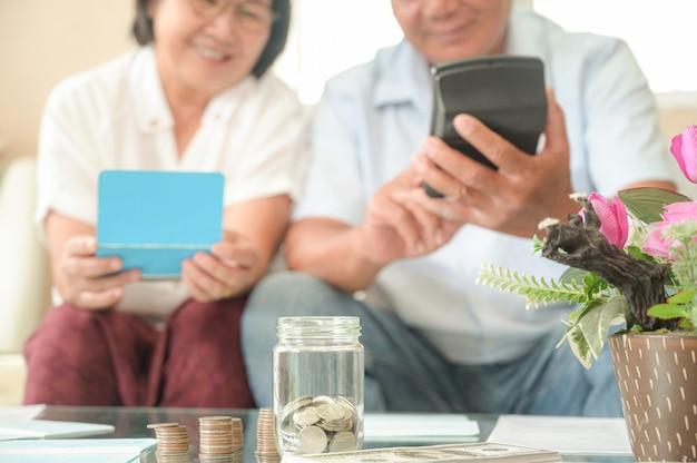Homens e mulheres asiáticos velhos sentam-se no sofá, fazem planos financeiros. Foto Premium