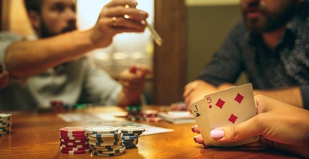 Homens e mulheres jogando jogo de cartas. conceito de pôquer, entretenimento noturno e emoção Foto gratuita