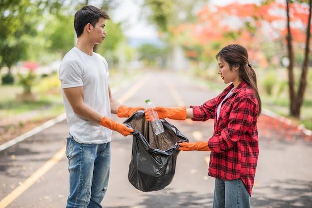 Homens e mulheres se ajudam a coletar lixo. Foto gratuita