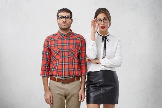 Homens e mulheres sérios em óculos e roupas formais, têm expressões intrigadas e rígidas Foto gratuita