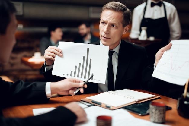 Homens estão olhando para gráficos e tabelas Foto Premium