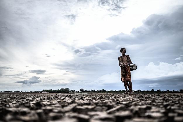 Homens idosos encontram peixes em solo seco, aquecimento global Foto gratuita