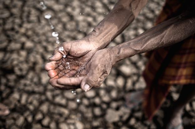 Homens idosos são expostos à água da chuva em clima seco e aquecimento global Foto gratuita