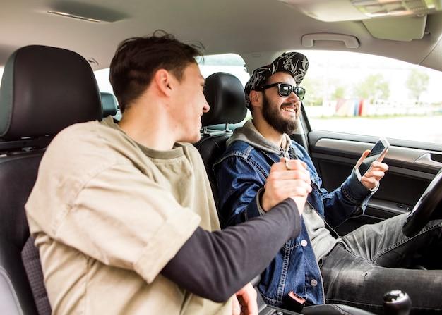 Homens jovens cumprimentando uns aos outros no carro Foto gratuita