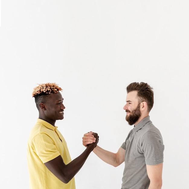 Homens jovens de cópia-espaço, apertando as mãos Foto gratuita