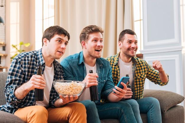 Homens jovens sentado no sofá assistindo evento esportivo na televisão em casa Foto gratuita