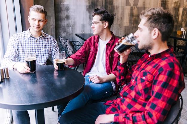 Homens jovens sentados juntos bebendo a cerveja com seu amigo Foto gratuita