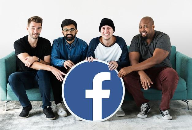 Homens mostrando um ícone do facebook Foto gratuita