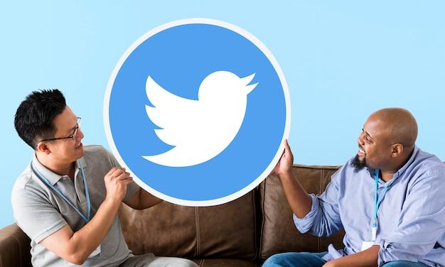 Homens mostrando um ícone do twitter Foto gratuita