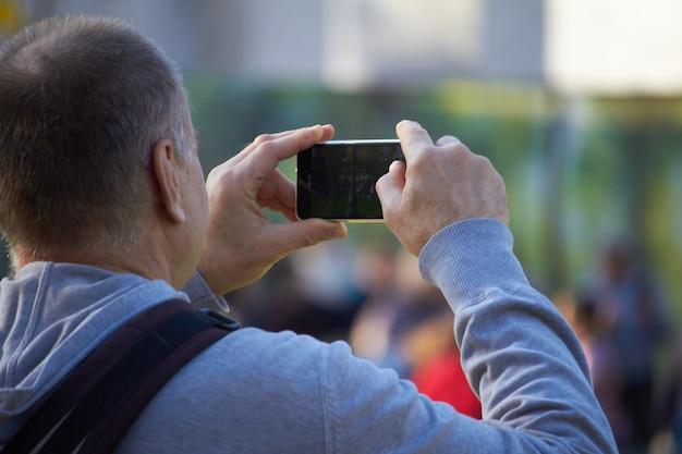 Homens na rua fotografando com telefone celular, plano de fundo é blured cidade Foto Premium