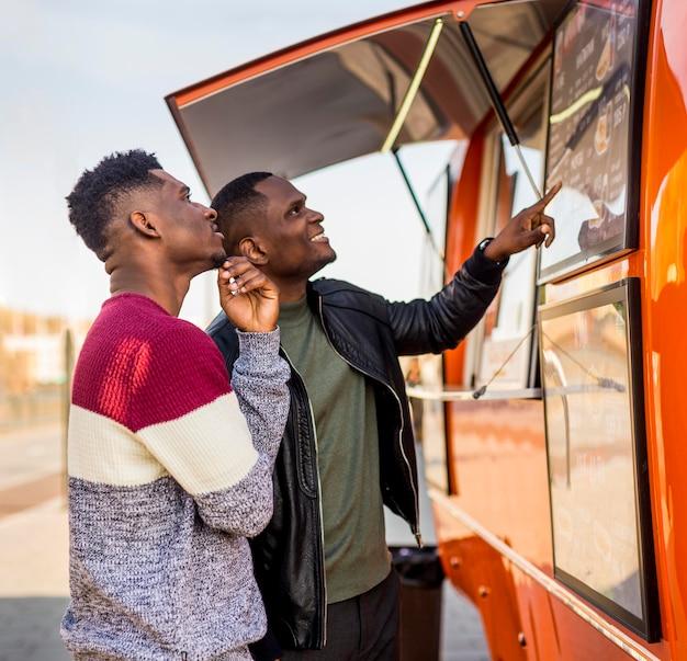 Homens no meio do tiro lendo cardápio de food truck Foto gratuita