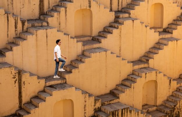 Homens que cruzam os poços em degraus de chand baori em jaipur na índia. Foto Premium