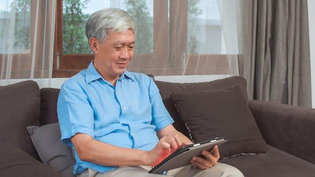 Homens sênior asiáticos que usam a tabuleta em casa. informação masculina chinesa sênior asiática da busca sobre como a boa saúde no internet ao encontrar-se no sofá no conceito da sala de visitas em casa. Foto gratuita