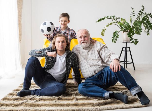 Homens sentados no tapete e assistindo futebol Foto gratuita