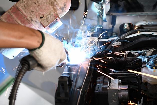 Homens soldador parte automotiva - oficina de reparação automóvel Foto Premium